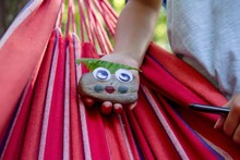 Closeup Of A  Girl Holding A Painted Rock With Googly Eyes