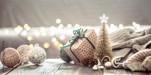 Christmas tree decorations over Christmas lights bokeh in home on wooden table with sweater on a background and decorations Wallpaper Mural