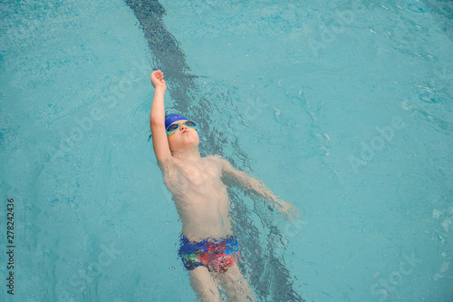 top view of a 7-year boy swimming backstroke in a swimming pool Canvas Print