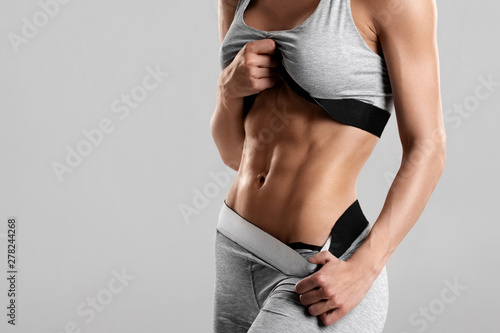 Fotomural  Fitness woman showing abs and flat belly, isolated