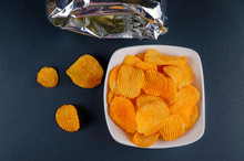 Delicious Golden Paprika Chips In A Bowl With A Bag, Flat Lay