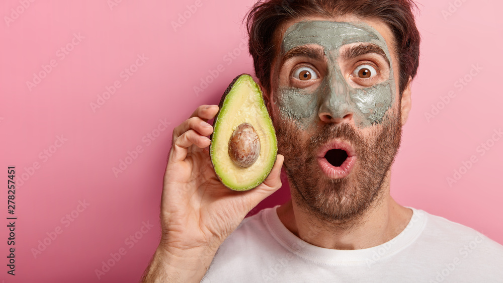 Fototapety, obrazy: Spa and beauty concept. Cropped image of handsome man stares with widely opened eyes at camera, applies natural clay mask on face, holds slice of avocado, visits spa salon, isolated on pink wall