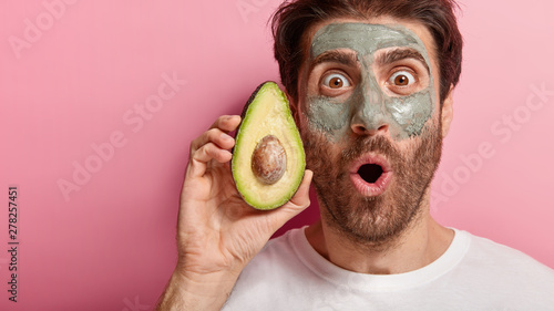 Poster Ecole de Danse Spa and beauty concept. Cropped image of handsome man stares with widely opened eyes at camera, applies natural clay mask on face, holds slice of avocado, visits spa salon, isolated on pink wall