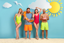 Four Positive Friends Stand Together On Beach, Hold Swim Equipment, Have Fun On Hot Day, Make Photo, Women Wears Bathing Suits, Men Trunks, Enjoys Spare Time. Holiday, Season, Travel Concept