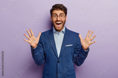 Принти на полотні Cheerful male banker in elegant outfit, smiles and shows palms, happy to meet with former colleague, isolated on purple background