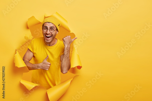 Fototapeta Smiling delighted guy points away, points with thumb and shows okay gesture, indicates at direction, wears yellow hat, t shirt, poses in ripped paper hole, has positive expression. Promotion concept obraz na płótnie