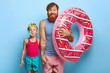 canvas print picture - Indoor shot of delighted caring father in striped vest and shorts, holds inflated swimring, touches hand of little daughter in snorkel mask, have fun in water park, enjoy bathing, stand over blue wall