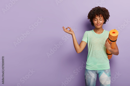 Keuken foto achterwand Ontspanning Young relaxed dark skinned woman practices yoga, meditates indoor for feeling relaxation, has eyes closed, holds fitness mat, dressed in active wear, isolated on purple background blank space on left
