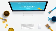 Concept Of A Modern Web Design Studio With Color Brushes And Color Boxes On A Clean Desk. Modern Web Site On Computer Display Painted With Colors.