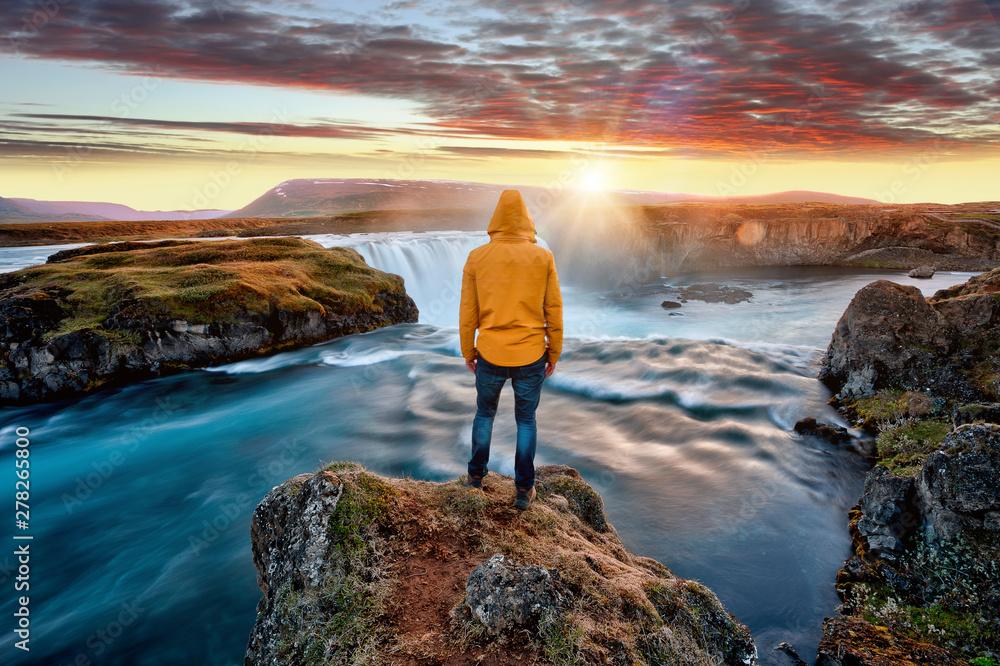 Fototapeta Man standing by amazing Godafoss waterfall in Iceland during sunset, Europe