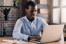 Young African American Business Man Sitting In Loft Office Or Cafe, Working On New Online IT Startup Project, Using Laptop