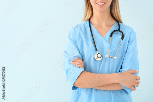 Carta da parati  Female nurse with stethoscope on color background