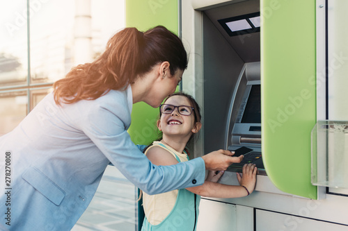 Obraz na plátne Young mother elegantly dressed with her daughter using ATM machine on city street