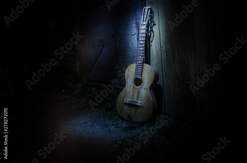 An wooden acoustic guitar is against a grunge textured wall. The room is dark with a spotlight for your copyspace. - 278272015