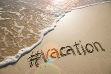 "Modern Travel Message For The Beach With A Social Media-friendly Hashtag Written With The Word ""vacation"" In Smooth Sand With Incoming Wave"