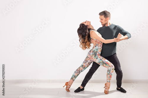 Poster Dance School Social dance concept - Active happy adults dancing bachata together over white background with copy space
