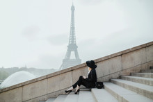 Young Woman And The Eiffel Tower Behind