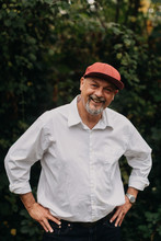 Portrait Of Older Man In Red Baseball Hat Laughing