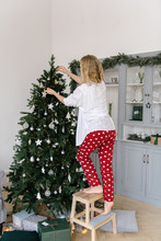 Woman On Steps Decorating Christmas Tree