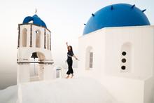 Girl Keeping Her Balance Near Orthodox Church At Santorini, Greece
