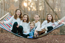 A Group Of Kids Hanging Out On A Hammock