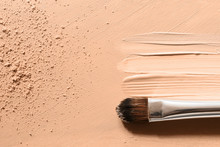 Makeup Foundation Background With Beige Liquid Foundation, Concealer Smudges, Face Powder And Cosmetic Makeup Brush
