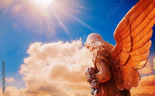 Foto  Ancient statue of guardian angel in sunlight as a symbol of strength, truth and faith
