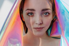 Surreal Portrait Of Young Pretty Female With Holographic Foil And Unusual Lightning Looking At Camera