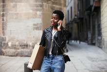 Cool Woman Using Phone Holding A Package On The Street.