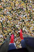 A Woman Walking In Red Rain Boots Through Autumn Leaves