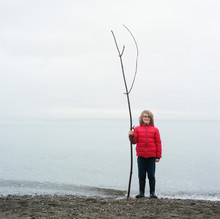 Boy Holds A Rather Long Stick On A Gravel Beach On Bainbridge Island