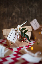 Tag, Leaves And Berries On Present Wrapped In Paper Bag
