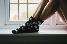 Legs And Feet In Christmas Socks On A Windowsill.