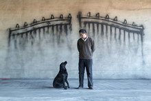 A Man And Dog In Front Of A Wa...