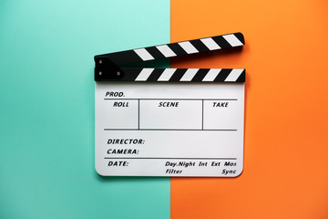movie clapper on color table background; film, cinema and video photography c...
