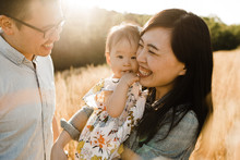 Happy Asian Family Snuggling, Cuddling And Being Playful Outdoors