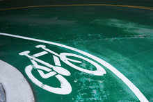 Bike Sign On The Road In A Green Pavement. Curve Of The Entrance Of Parking Area.