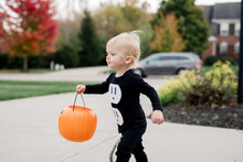 Toddler In An Electrical Outlet Costume Determinedly Walking With His Halloween Candy Loot