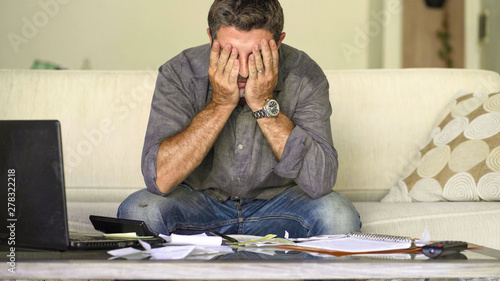 Obraz na plátně stressed and desperate man at home living room couch doing domestic accounting w