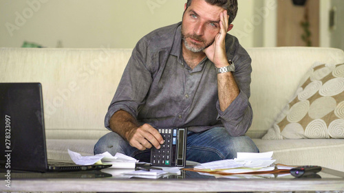 Fotomural stressed and desperate man at home living room couch doing domestic accounting w