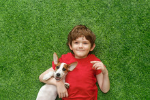 Child Embracing Puppy Jack Russell And Lying On Green Carpet.