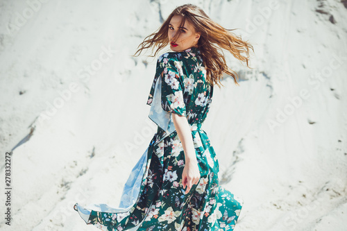 Attractive slender girl in green swimwear posing on white sand beach. Young woman in bikin rests on vacation at sandy ocean shore. Concept travel, swimsuit