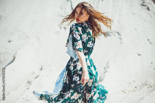 Attractive slender girl in green swimwear posing on white sand beach Fototapeta