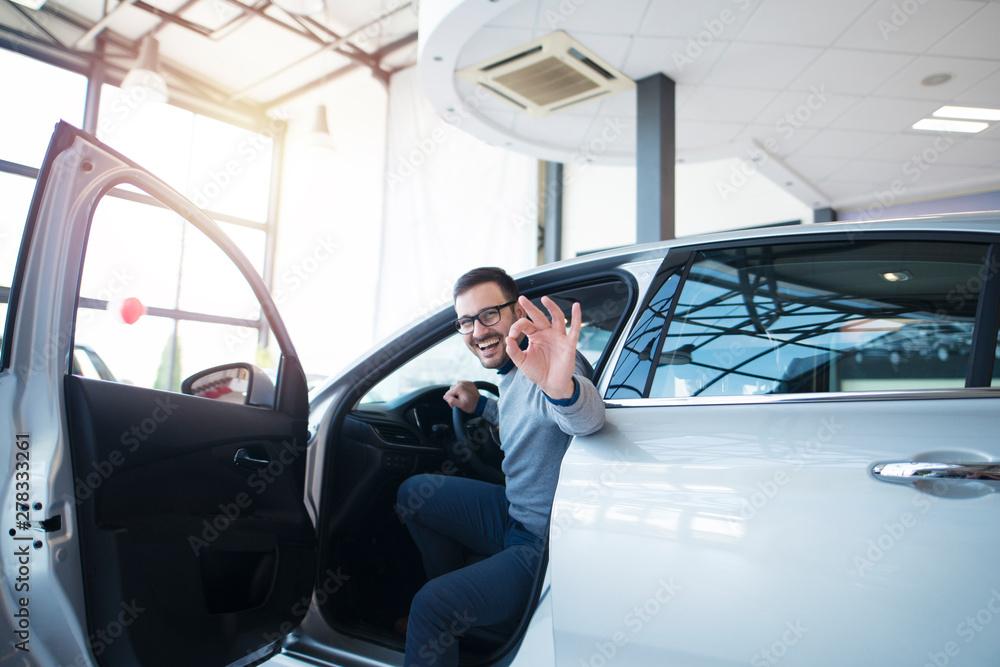 Fototapeta Car dealer or car buyer sitting in brand new vehicle showing okay hand gesture. Satisfied customer at vehicle dealership showroom.