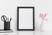 Black Frame Mockup With Pink Oleander In A Glass Vase And Workspace Accessories On A White Table.Portrait Orientation.