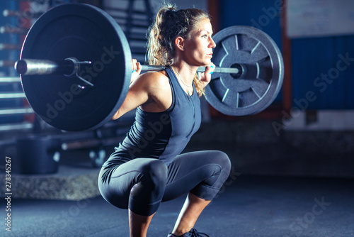Fototapeta Woman weightlifting on training