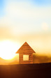 Conceptual paper house isolated on the sunset sky