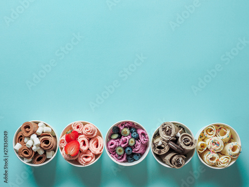 Fotomural rolled ice creams in cone cups on blue background