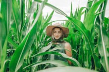 Beautiful Girl In Straw Hat With Her Eyes Closed Is In The Green Corn Field.
