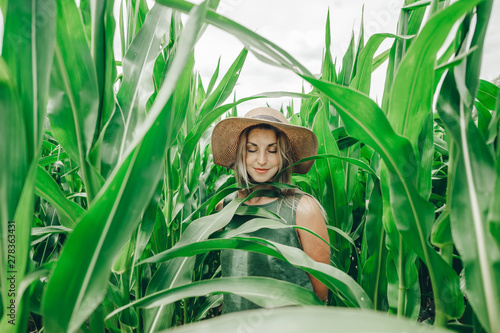 Canvas Print Beautiful girl in straw hat with her eyes closed is in the green corn field